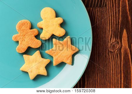 Gingerbread cookies man and star shape in turquoise plate on wooden table with copyspace