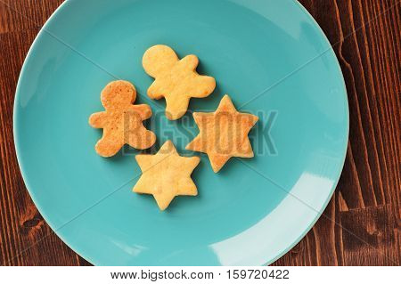 Gingerbread cookies man and star shape in turquoise plate on wooden table overhead view
