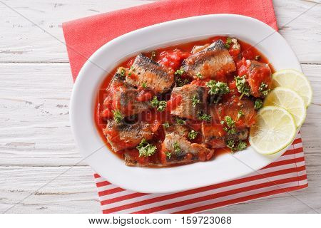 Sardines In Tomato Sauce, Decorated With Lime And Parsley Close-up. Horizontal Top View