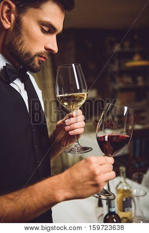 Wine critic is smelling white wine in goblet. He holding red liquor at other hand