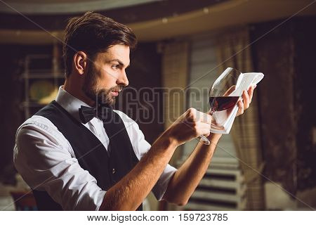 Liquor critic is taking wineglass with red nectar on white napkin and looking attentively