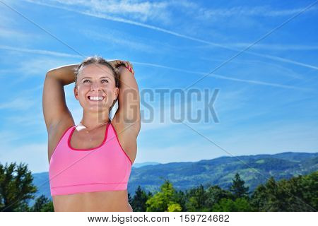 Young sports woman stretching her arms up while exercising on a mountain with a blue sky.