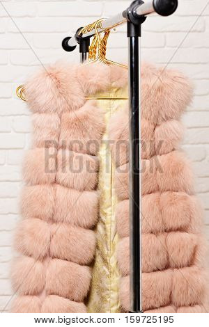 fashionable luxurious waist coat of fur hanging on rack on golden hangers on brick wall studio background