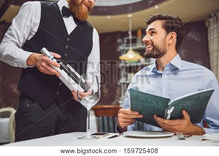 Attentive client is sitting at table and choosing sort of beverage. He smiling to man holding flask with wine