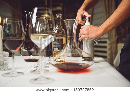 Waiter is opening bottle with white wine. Different utensil are on board