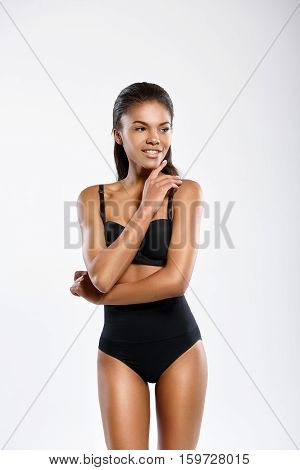 Pure beauty. Young mulatto woman is standing isolated on background. She is smiling