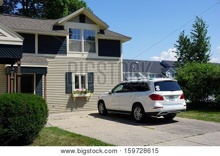 HARBOR SPRINGS, MICHIGAN / UNITED STATES -August 3, 2016: A Mercedes-Benz GL-450 is parked in a driveway of a home in Harbor Springs.