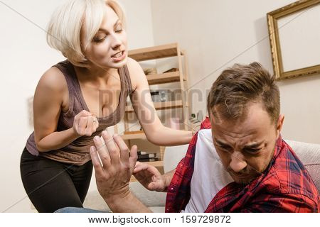 Couple man and woman having conflict while spending time at home. Family stress and family conflict. Blond lady screaming and shouting at her husband.
