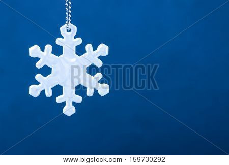 Cute white safety reflector in the form of snowflakes on blue background. Necessary equipment to pedestrians for walks during dark conditions