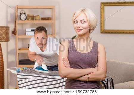 Portrait blond woman with crossed arms smilinf for camera while her handsome man using iron for ironing clothes on background at home.