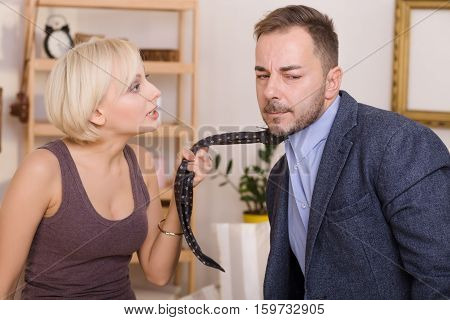 Man under pressure of his wife listening to her arguments. Coupe man and woman having quarrel. Blond lady keeping his tie. Family concept.