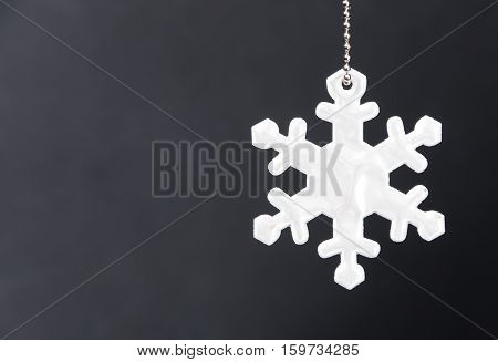 Cute white safety reflector in the form of snowflakes on black background. Necessary equipment to pedestrians for walks during dark conditions