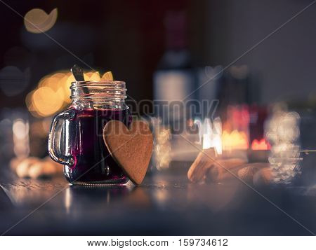 A glass of hot mulled wine, also known as Gluhwein and a gingerbread cookie och defocused Christmas decorated background. Shot with a shallow depth of field.