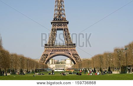 Warm spring day in Paris. People relaxing on the Champ de Mars near the Eiffel Tower