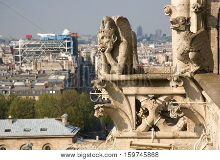 Close-up of two gargoyles on the top of Notre-Dame de Paris with Centre Georges Pompidou in the background