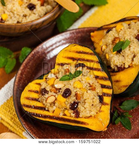 Pumpkin Acorn Stuffed with Quinoa, Nuts and Dried Fruit. Selective focus.
