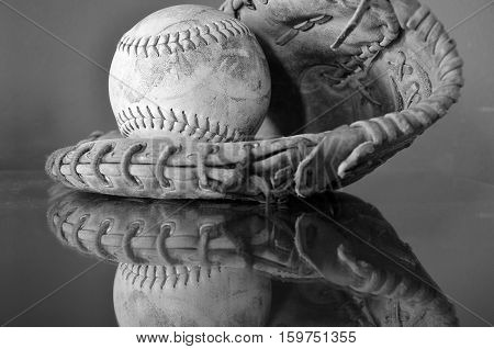 A black and white image of an old leather baseball and baseball glove.