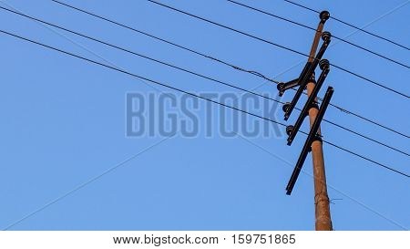 Electric pole or power pole with old power line on blue sky background.