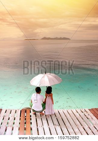 Back view of father and daughter at wooden terrace with umbrella to hide from sun. dad and daughter watch school of fish swim near port Indo-pacific ocean Southeast Asia