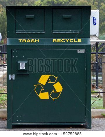 San Francisco CA - October 21 2016: Combination trash and recycling can enclosed in animal proof bin to prevent wildlife from rummaging through the trash. Hand sanitizer dispenser attached to side.