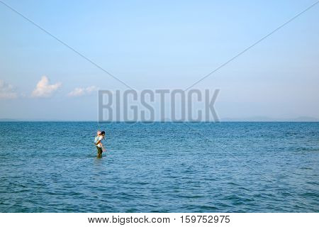 Seascape of lovely Asian family father giving daughter piggyback ride on his back walking on high tide. Cute girl with dad playing outdoor. Copy space for fathers day concept.