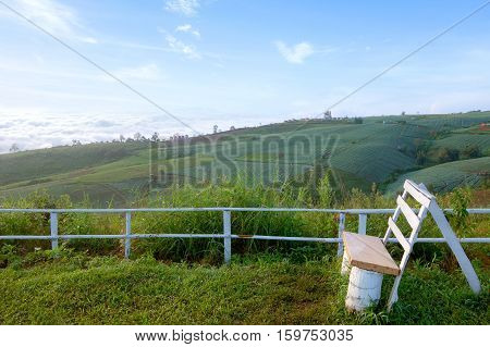 A handmade wooden chair on beautiful outdoor space with a view of sea of mist and vegetable farm in the morning Phutabberk Petchabun Thailand. Copy space.
