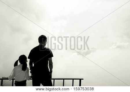 Silhouette of Asian father and daughter standing on terrace to watch sea of mist. Power of sunlight in the morning. Fathers day concept Phutabberk Petchabun Thailand. Copy space.