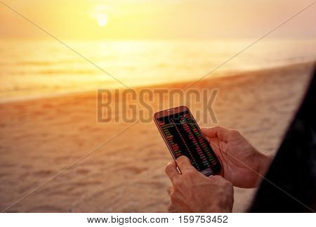 Hand of business man making trading online on the smart phone with light of sunset on tropical beach background. New ways to make economy and trading. Phone with blur trading screen copy space.