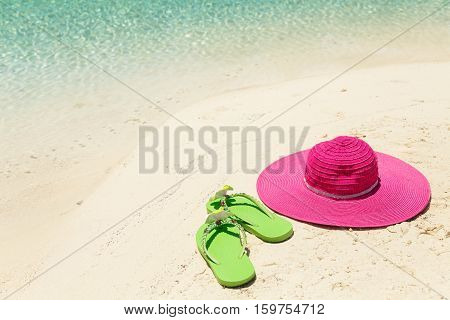 Pink beach hat and green slippers in the golden sand by sea shore