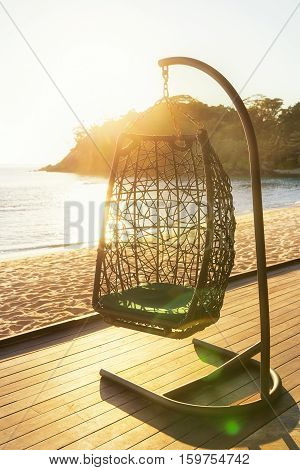 Cozy hanging resting chair on decking by sea side at evening sun light