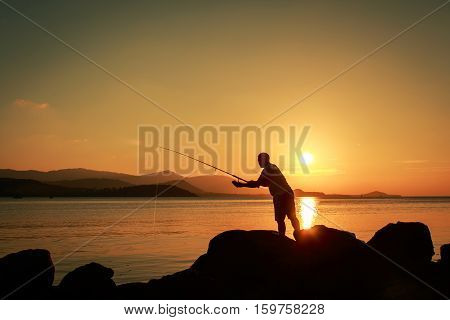Young man standing on stone and fishing at sea sunset background