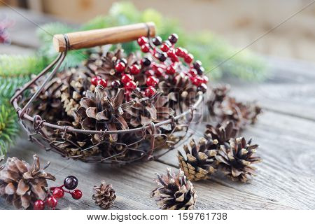 Christmas concept: full basket of pine cones and red holly berries and spruce branches on the background of old unpainted wooden boards. Christmas wallpaper