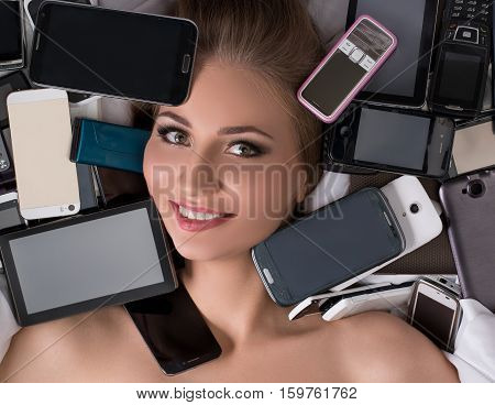 Digital technology as fetish. Smiling nude girl with lot of smartphones