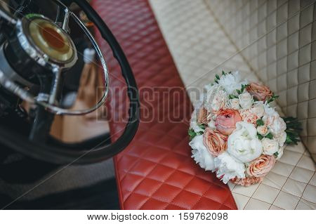 Bouquet of wedding flowers on the car seat
