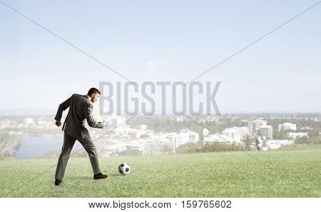 Businessman kicking soccer ball . Mixed media
