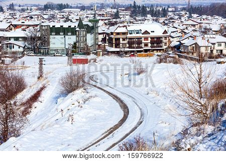 Winter road, houses with snow roofs panorama of bulgarian ski resort Bansko, Bulgaria