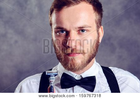 Bearded Man In White Shirt And Bow Tie Showing Shaver