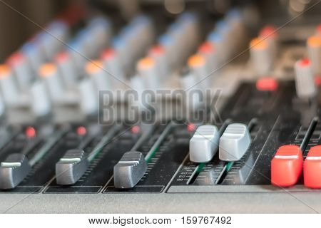 close up electronic professional sound mixer control panel in music studio with channel console and media button for record music or live radioselective focus.