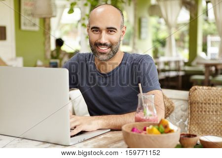 Bearded Businessman Dressed Casually Checking Email On His Laptop During Breakfast, Sitting At Nice