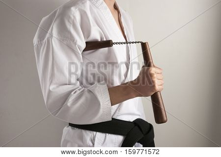 Karate fighter is ready position facing the right side with a nunchaku under his arm.