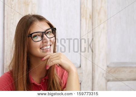 Cheerful Attractive Caucasian Girl In Rectangular Glasses Posing Indoors Against Wooden Wall Backgro