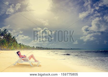 brown-haired middle-aged woman lying on a lounger by the ocean shore