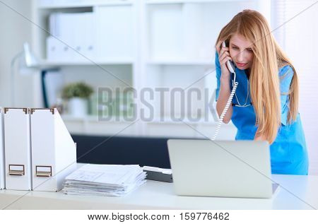 Female doctor talking on phone in diagnostic center .