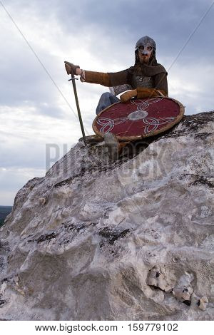 Knight sitting on a rock with a sword against blue cloudy sky