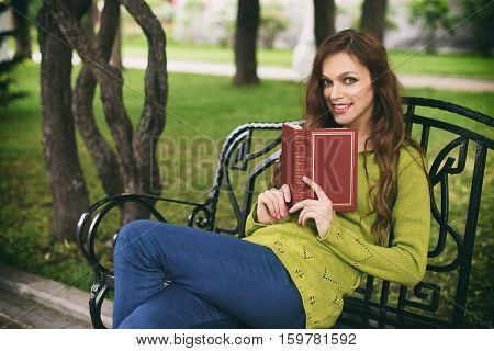 Beautiful Woman At Park Reading A Book On A Bench