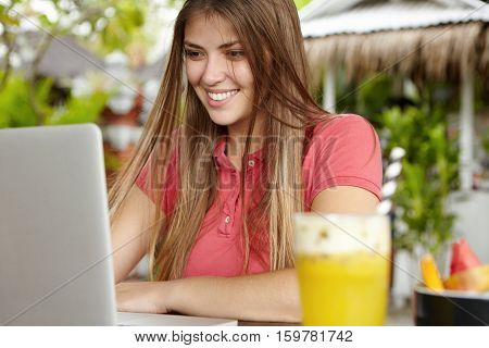 Happy Young Woman With Long Loose Hair Sitting In Front Of Laptop Computer Using Free Wireless Inter
