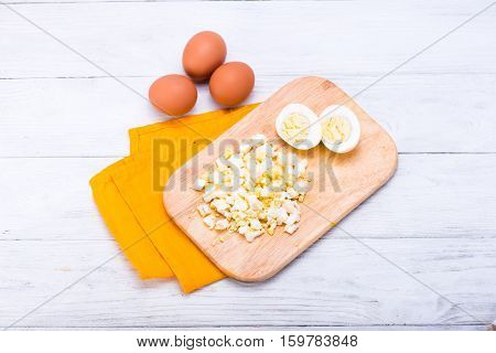 Cooked egg sliced on wooden board. White table with yellow napkin. Top view.