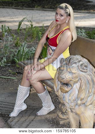 the woman sits on a bench near a stone lion a subject beautiful women