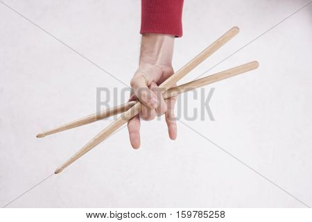 Hands holding drumsticks on a white background