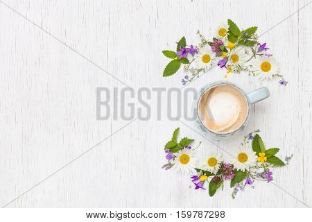 Top view on beautiful wild flowers in shape of wreath and a cup of cappuccino coffee on white wooden background. Summer flowers leaves petals and coffee on the table. Flat lay